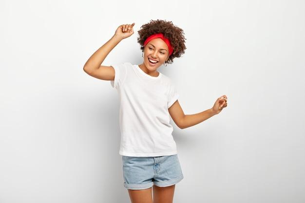 Adolescente despreocupada e satisfeita se diverte, dança alegremente com os braços levantados, se divertindo e se divertindo, usa roupas de verão