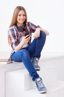 Adolescente despreocupado. linda garota adolescente segurando um telefone celular e sorrindo enquanto está sentada na escada