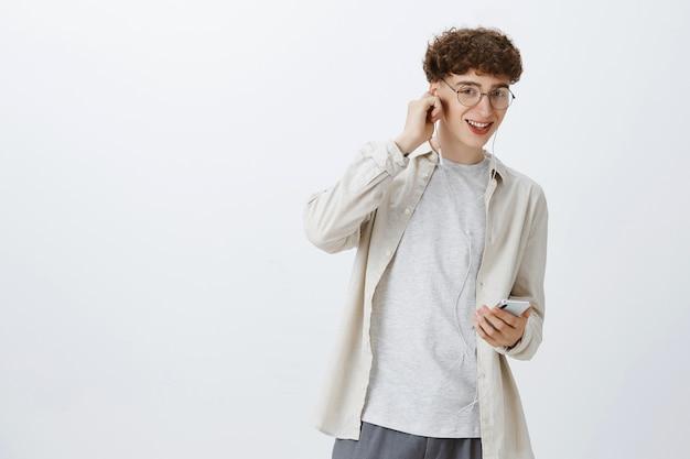 Adolescente despreocupado posando contra a parede branca
