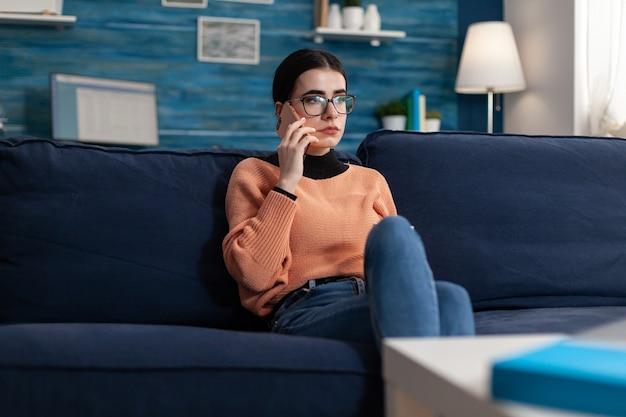 Adolescente disscusing no telefone sobre o exame universitário enquanto estava deitado no sofá na sala de estar. aluno falando em smartphone sobre tecnologia de internet durante quarentena de coronavírus, conversa casual gosip