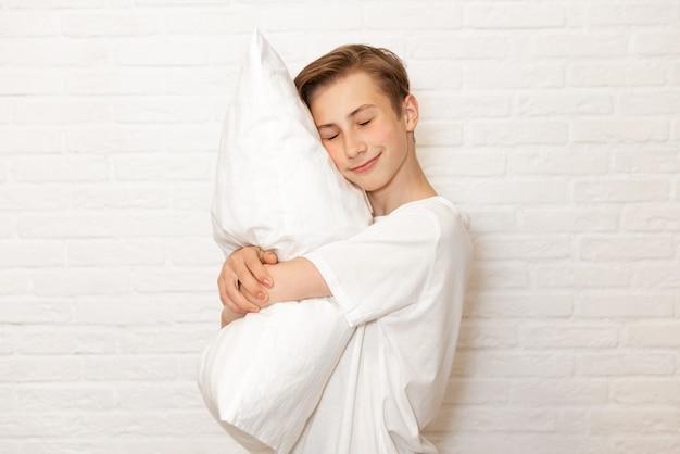 Adolescente do sexo masculino abraçando um travesseiro com os olhos fechados, isolado no branco