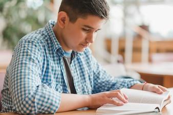 Adolescente do sexo masculino, aproveitando a leitura