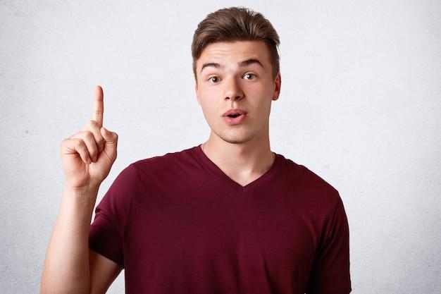 Adolescente do sexo masculino atordoado com expressão de surpresa mantém o dedo dianteiro levantado