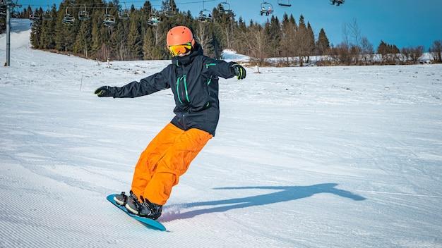 Adolescente do sexo masculino dando voltas com sua prancha de snowboard em um dia nublado