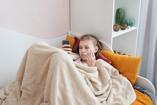 Adolescente doente, deitado na cama com termômetro usando telefone celular