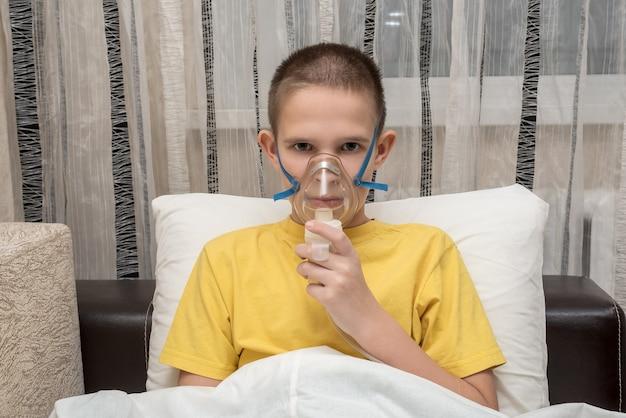 Adolescente doente em casa com uma máscara respiratória encontra-se no sofá. segura uma máscara com a mão.