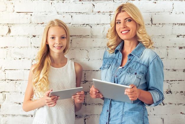 Adolescente e a mãe dela estão segurando tabuletas.