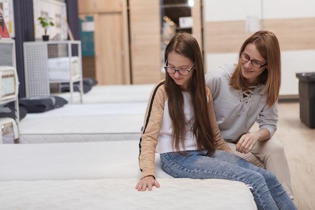 Adolescente e mãe escolhendo colchão ortopédico em loja de móveis