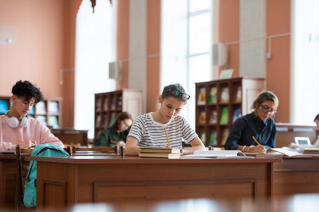 Adolescente e outros alunos da faculdade sentados em mesas na biblioteca e fazendo anotações em cadernos enquanto se preparam para o seminário