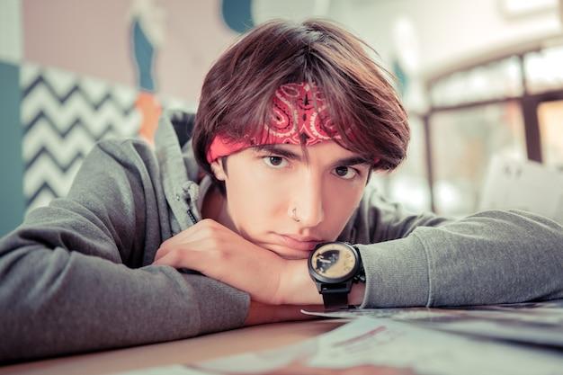 Adolescente elegante. adolescente usando lenço e relógio colocando a cabeça entre as mãos