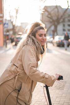 Adolescente elegante andando de scooter elétrico