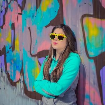 Adolescente elegante em óculos de sol coloridos posando perto de parede grafite
