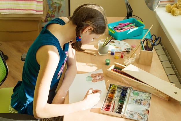 Adolescente em casa desenha aquarela
