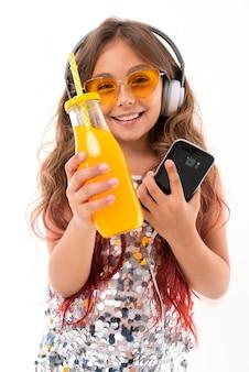 Adolescente em óculos de sol amarelos, grandes fones de ouvido brancos, com smartphone preto na mão esquerda e garrafa de suco de laranja na mão direita isolada