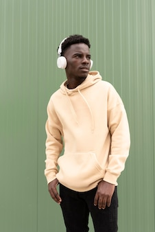 Adolescente em plano médio posando com fones de ouvido