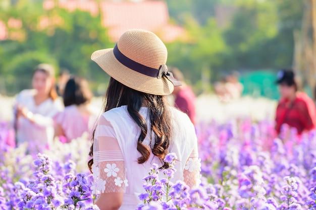 Adolescente em um jardim de flores jovem garota asiática feliz no campo de flores margaret aster