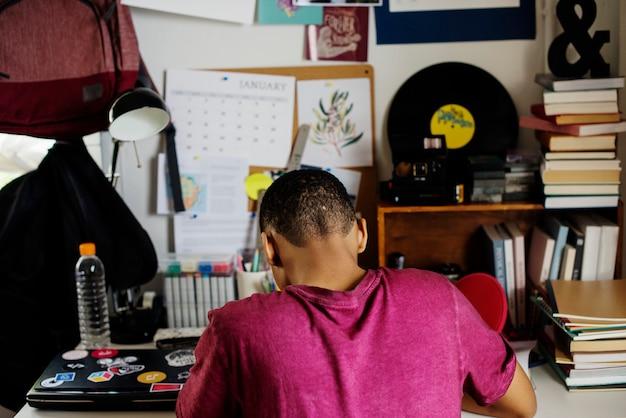 Adolescente em um quarto fazendo trabalho estressado e frustrado