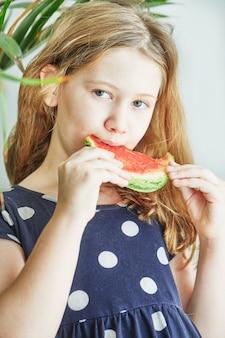 Adolescente em um vestido azul com bolinhas, comendo uma melancia.