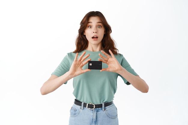 Adolescente empolgada conseguiu seu primeiro cartão de crédito, mostrando-o nas mãos e olhando espantada na frente, em pé de camiseta e jeans contra a parede branca