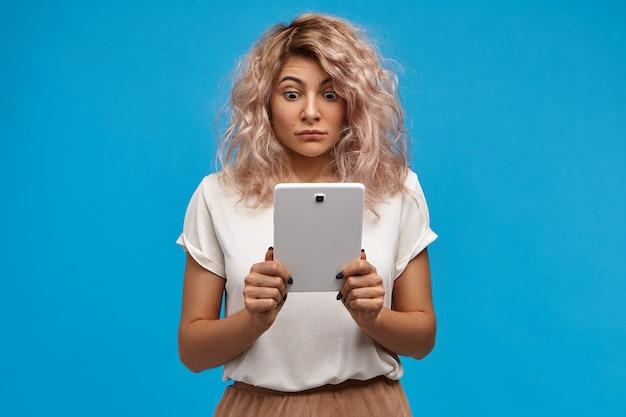 Adolescente engraçada e emocional com piercing no nariz e cabelo rosado, arregalando os olhos enquanto olha para a tela do tablet digital