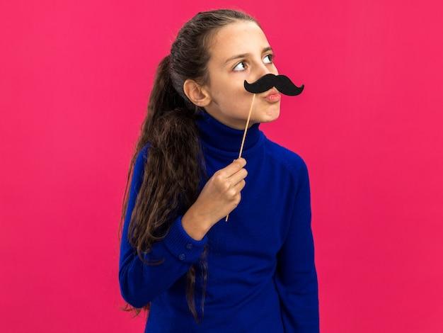 Adolescente engraçada segurando um bigode falso acima dos lábios, olhando para o lado com os lábios franzidos, isolados na parede rosa com espaço de cópia