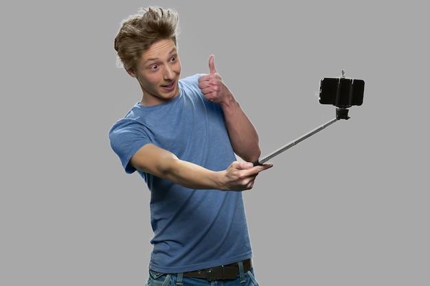 Adolescente engraçado usando monopé. cara adolescente mostrando o polegar para cima gesto enquanto toma selfie contra um fundo cinza.