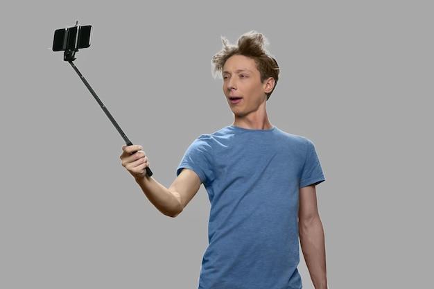 Adolescente engraçado usando selfie stick. menino adolescente caucasiano fazendo selfie com monopé contra um fundo cinza. pessoas, tecnologia moderna, diversão.