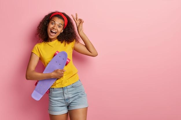 Adolescente entusiasmada com cabelo encaracolado posando em uma camiseta amarela