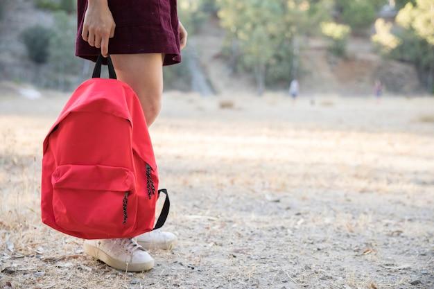 Adolescente, esperando, com, mochila, em, mão, parque