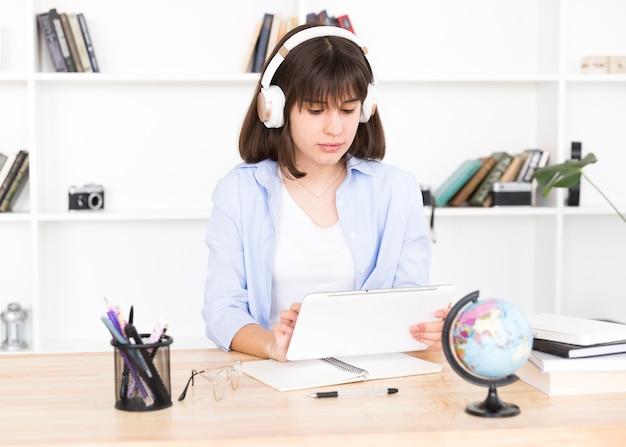 Adolescente, estudante, em, fones, sentando tabela, com, tabuleta, em, mãos