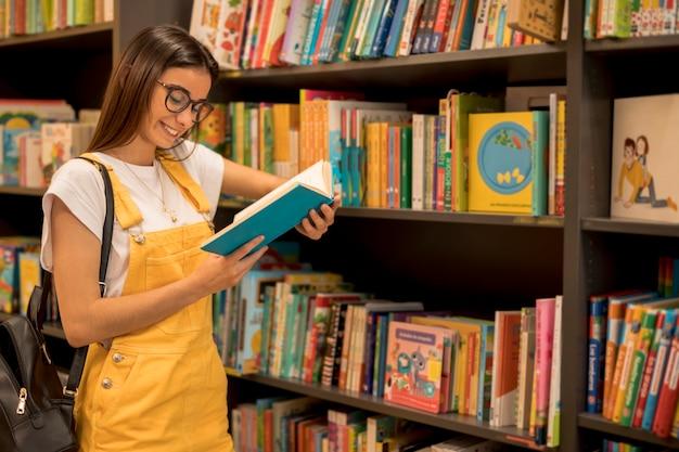 Adolescente estudante lendo livro encostado na prateleira