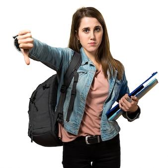 Adolescente, estudante, menina, segurando, livros, fazer, mau, sinal