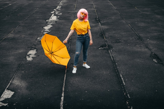 Adolescente étnico moderno segurando guarda-chuva amarelo brilhante