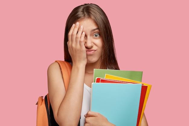 Adolescente europeu descontente cobre o rosto com expressão de frustração, sente-se cansado