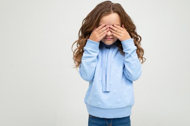 Adolescente europeu em um capuz azul cobriu os olhos com as mãos em um fundo branco com espaço de cópia