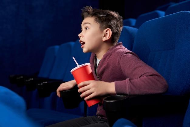 Adolescente excitada com assistindo filme de ação no cinema