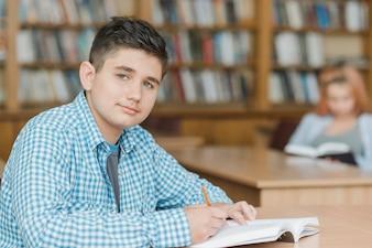Adolescente, fazendo, dever casa, em, biblioteca