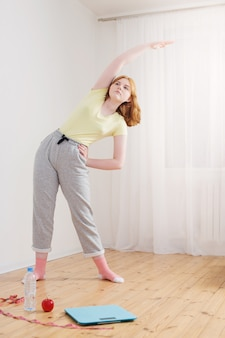 Adolescente fazendo esportes em casa, balanças eletrônicas no chão