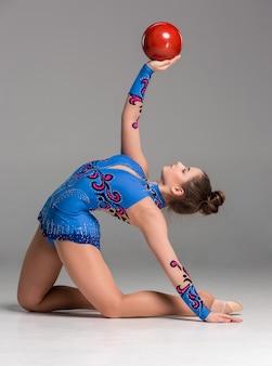 Adolescente fazendo exercícios de ginástica com a bola vermelha sobre um fundo cinza