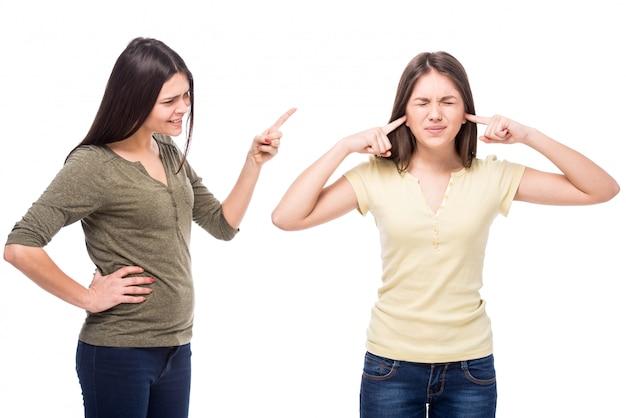 Adolescente fechou as orelhas com as mãos enquanto a mãe dela grita com ela.