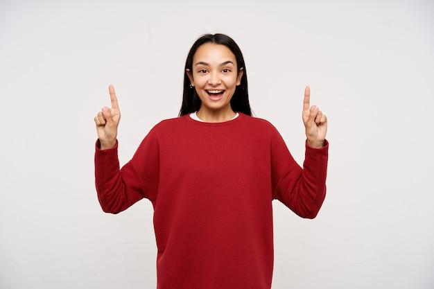 Adolescente, feliz, alegre mulher asiática com cabelo comprido escuro. vestindo um suéter vermelho e apontando para o espaço da cópia. olhando para a câmera com um grande sorriso, isolado sobre fundo branco