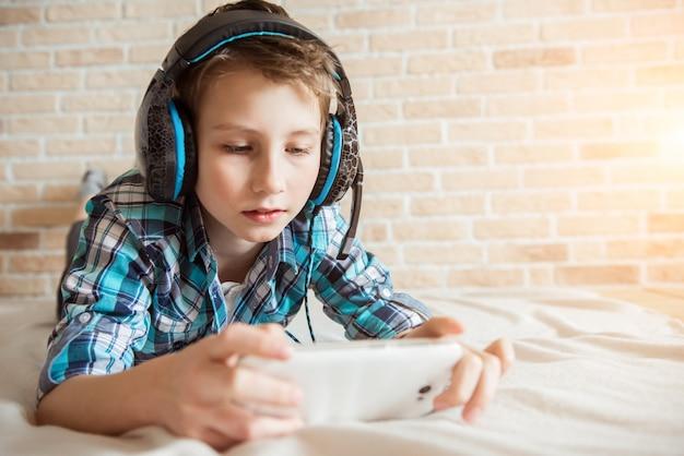 Adolescente feliz brincando no smartphone com fone de ouvido conectado