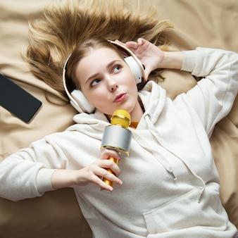 Adolescente feliz cantando usando microfone e fones de ouvido em fundo bege. canto de música de karaokê. treinamento vocal.