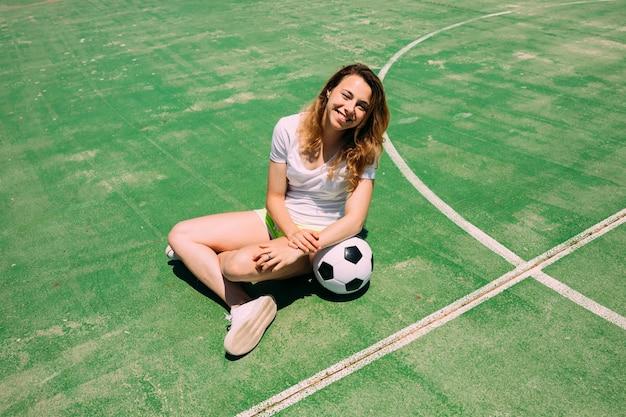 Adolescente feliz com bola no campo de futebol