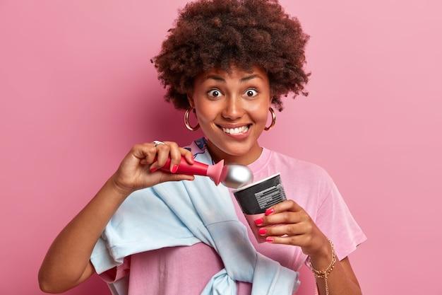 Adolescente feliz com cabelo afro, morde os lábios e come apetitoso sorvete de morango, parece positiva, gosta de sobremesa fria de verão, vestida casualmente, isolada sobre parede rosa