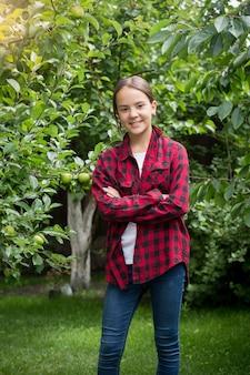 Adolescente feliz com camisa quadriculada vermelha posando no jardim de maçãs