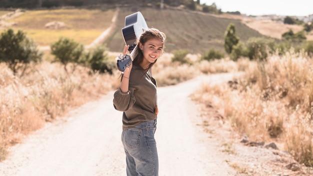 Adolescente feliz com pé de guitarra ao ar livre