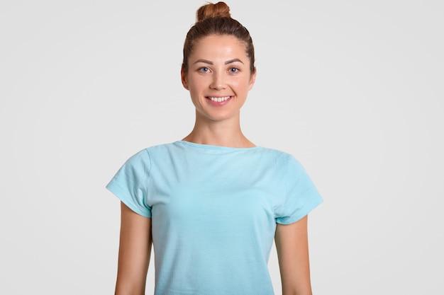 Adolescente feliz com sorriso, expressão encantada, veste camiseta casual, estar de bom humor, tem uma pele saudável, isolada sobre o branco. conceito de emoções positivas.