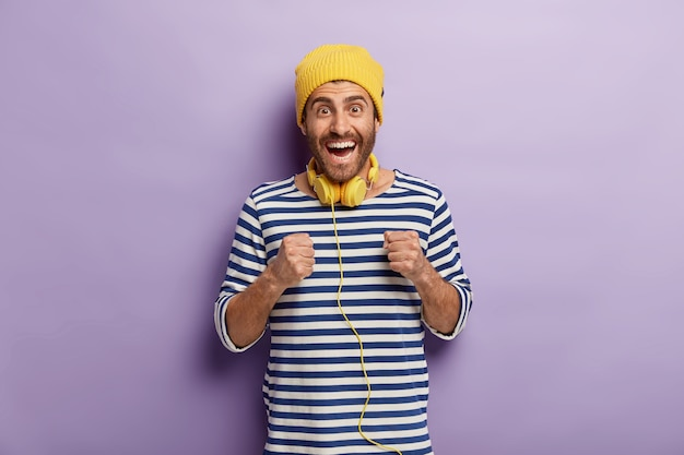 Adolescente feliz do sexo masculino cerrando os punhos, antecipando algo com imaptiene