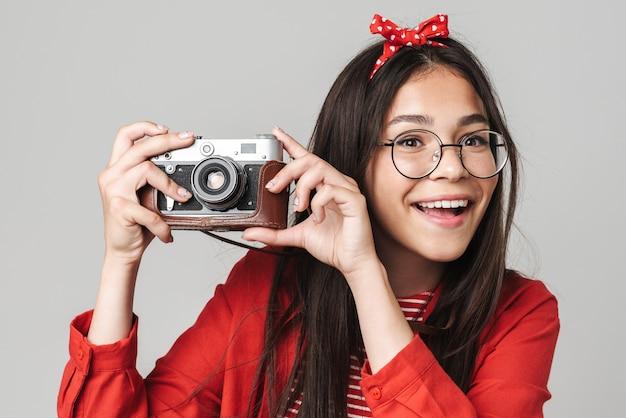 Adolescente feliz e fofa vestindo roupa casual em pé, isolada na parede cinza, tirando fotos com a câmera de retratos